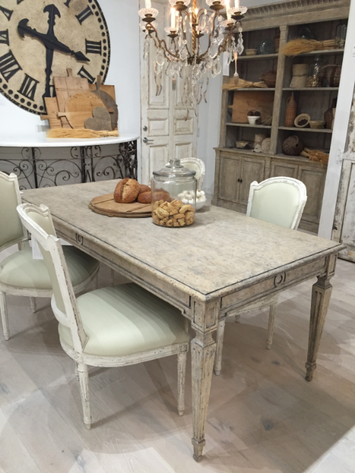 A reproduction French antique table surrounded by antique chairs at Eloquence.