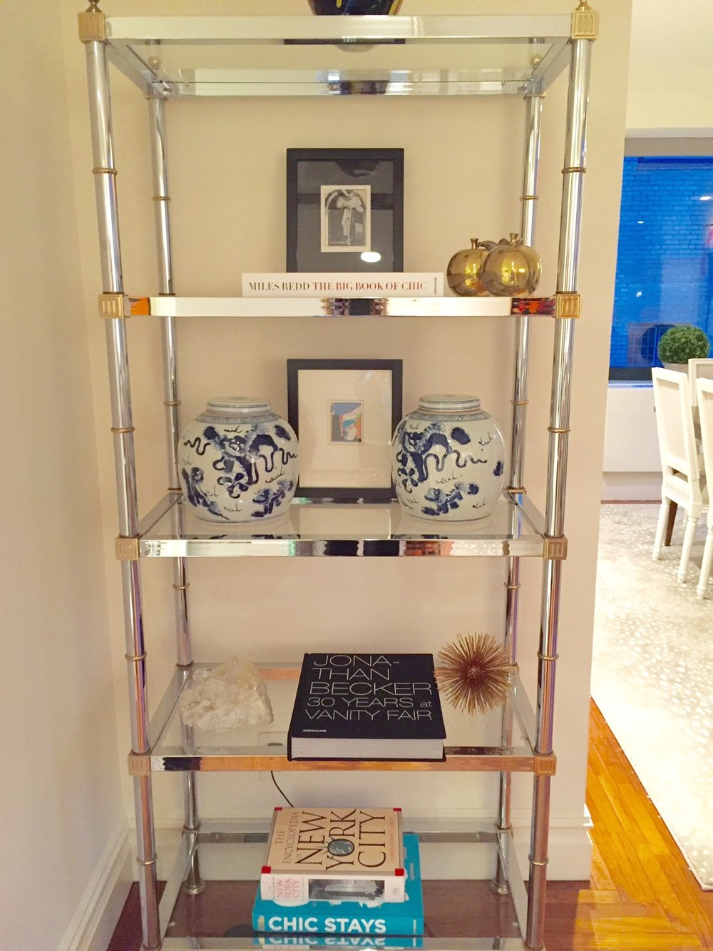 This chrome and brass mid-century Jansen style etagere from our collection adds a bit of visual interest to a small alcove and is a great place to display books, accessories and family photos.
